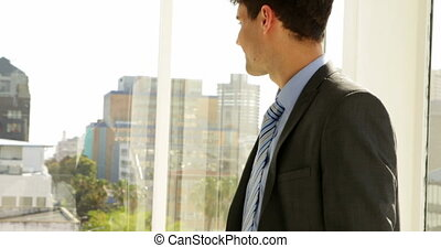 Businessman looking out his window then turning to camera in...