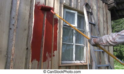painting old wooden farm house wall