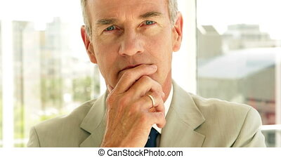 Thinking businessman looking at camera