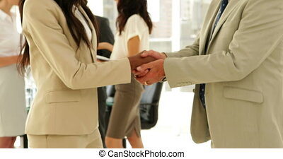 Business people talking together and shaking hands at the...