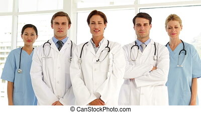Confident medical team looking at camera and giving thumbs...