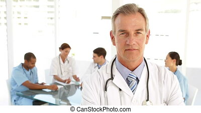 Doctor looking at camera and his staff behind him at the...