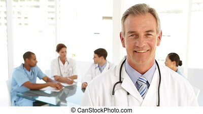 Happy doctor looking at camera and his staff behind him at...