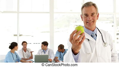 Mature doctor looking at camera holding an apple