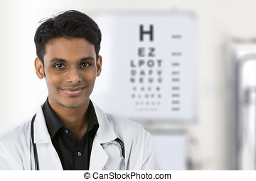 Indian doctor with an eye chart behind him - Indian doctor...