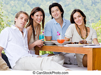 Friends Having Lunch - A group of four young adults sitting...