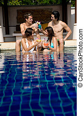 Friends In Pool - Four young adults sitting in a pool with...