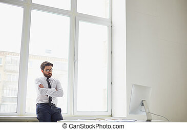 Serious office worker - Serious businessman standing by the...