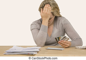 Credit Crisis - woman sitting at desk with credit cards and...