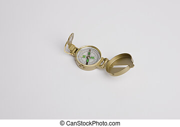 Golden compass on reflective surface with white background