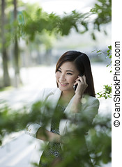 Asian Businesswoman using a smart phone Happy smiling...