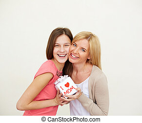 Happiness - Teenage girl and her mom with small present...