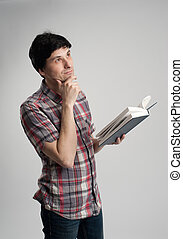 Thoughtful mid adult man with book looking up