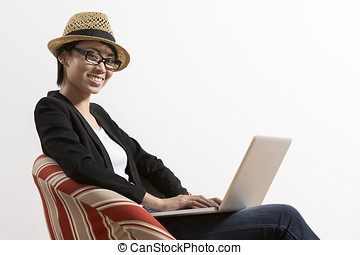 Happy Chinese woman sitting on a chair using laptop -...