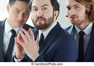 Irritation - Annoyed businessman looking at camera with his...