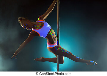 Pretty girl with luminous makeup dancing on pole
