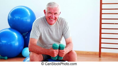 Elderly man lifting hand weights sitting on exercise ball in...