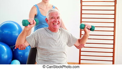 Elderly man lifting hand weights sitting on exercise ball...