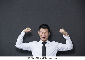 Chinese business man flexing his arms - Chinese business man...
