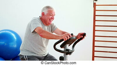 Elderly man using the exercise bike at the gym