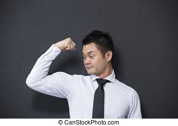Chinese business man flexing his large bicep Concept about...