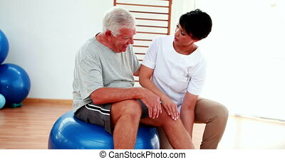 Smiling physiotherapist helping elderly patient bend knee at...