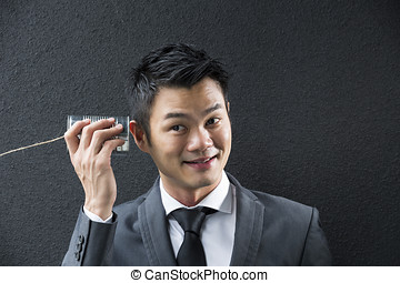 Chinese Business man Listening to a Tin Can Phone -...
