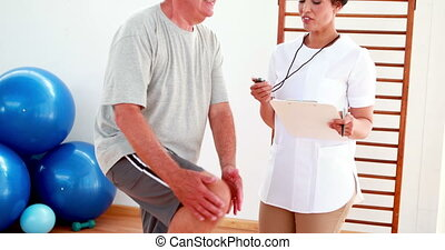 Smiling physiotherapist timing elderly patient with knee...