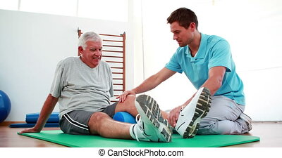 Physiotherapist helping patient with his knee mobility at...