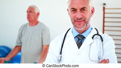 Smiling doctor looking at camera with patient exercising in...
