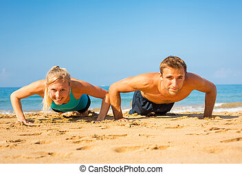 Couple doing push ups on the beach - Athletic couple doing...