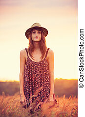 Beautiful woman in golden field at sunset, Fashion...