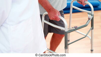 Smiling doctor talking with patient using zimmer frame at...