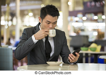 Chinese business man in a food court using his phone. -...
