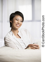 Young Chinese woman texting on couch - Pretty Chinese woman...