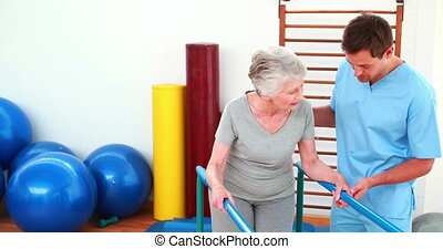 Physical therapist helping patient to walk with parallel...