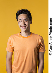 Portrait of Chinese man standing against yellow background....