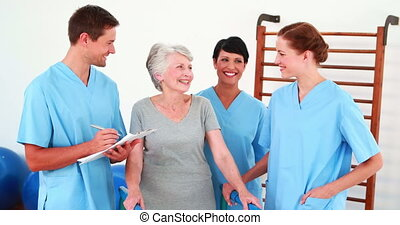 Elderly woman smiling and talking with her physical rehab...
