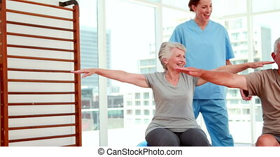 Senior citizens working out with physiotherapist at the gym