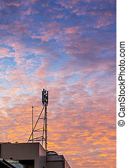 Telecom tower with  golden cloud on sunset