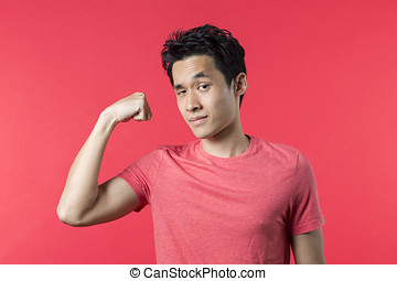 Young Chinese man standing flexing his bicep - Portrait of...