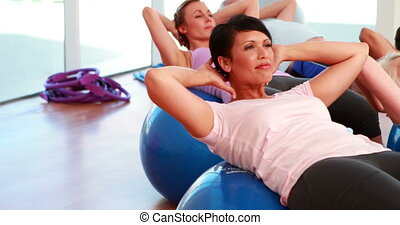 Exercise class doing sit ups on exercise balls at the gym