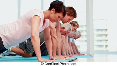 Exercise class doing push ups together at the gym