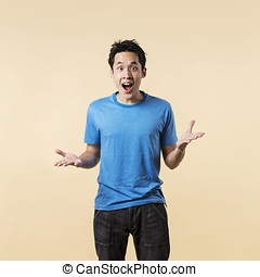 Surprised Chinese man standing against cream background -...