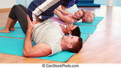 Yoga class having fun on exercise mats