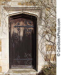 Wooden door set in stone wall - Old weathered wooden door...