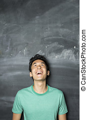 Happy Asian man looking above at empty blackboard - Closeup...