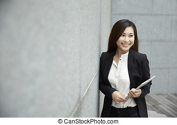 Chinese business woman with a tablet computer. Asian...