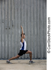 Sporty Young Asian man stretching outdoors in urban city.
