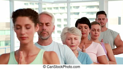 Yoga class standing with eyes closed at the gym